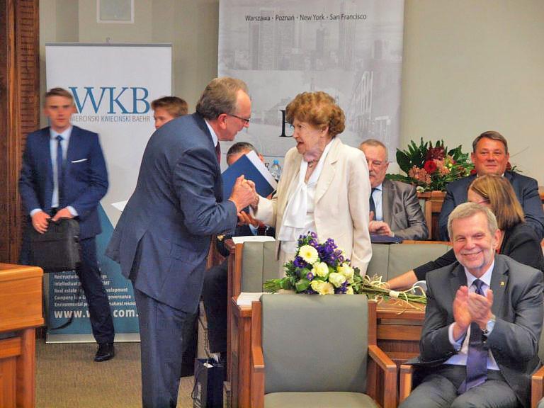 Mężczyzna gratuluje starszej kobiecie podczas prelekcji a uczestnicy wykładu biją brawa