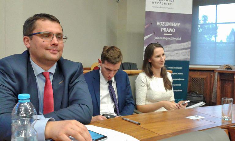 trzech uczestników wykładu siedzący przy ławce