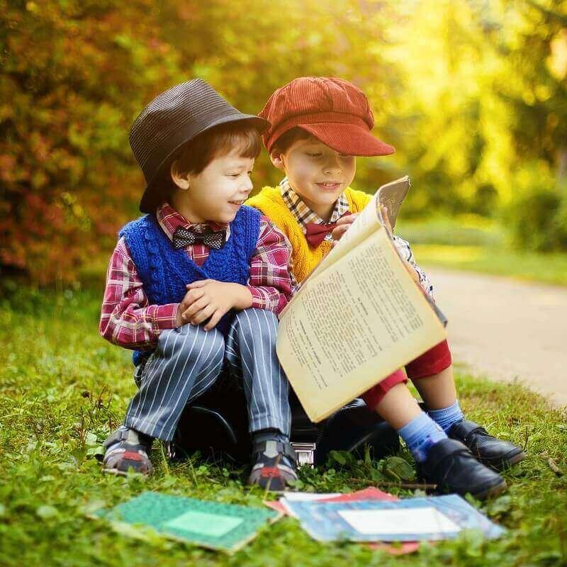 dwóch chłopców ubranych w staroświeckie ubranka czyta gazetę w parku
