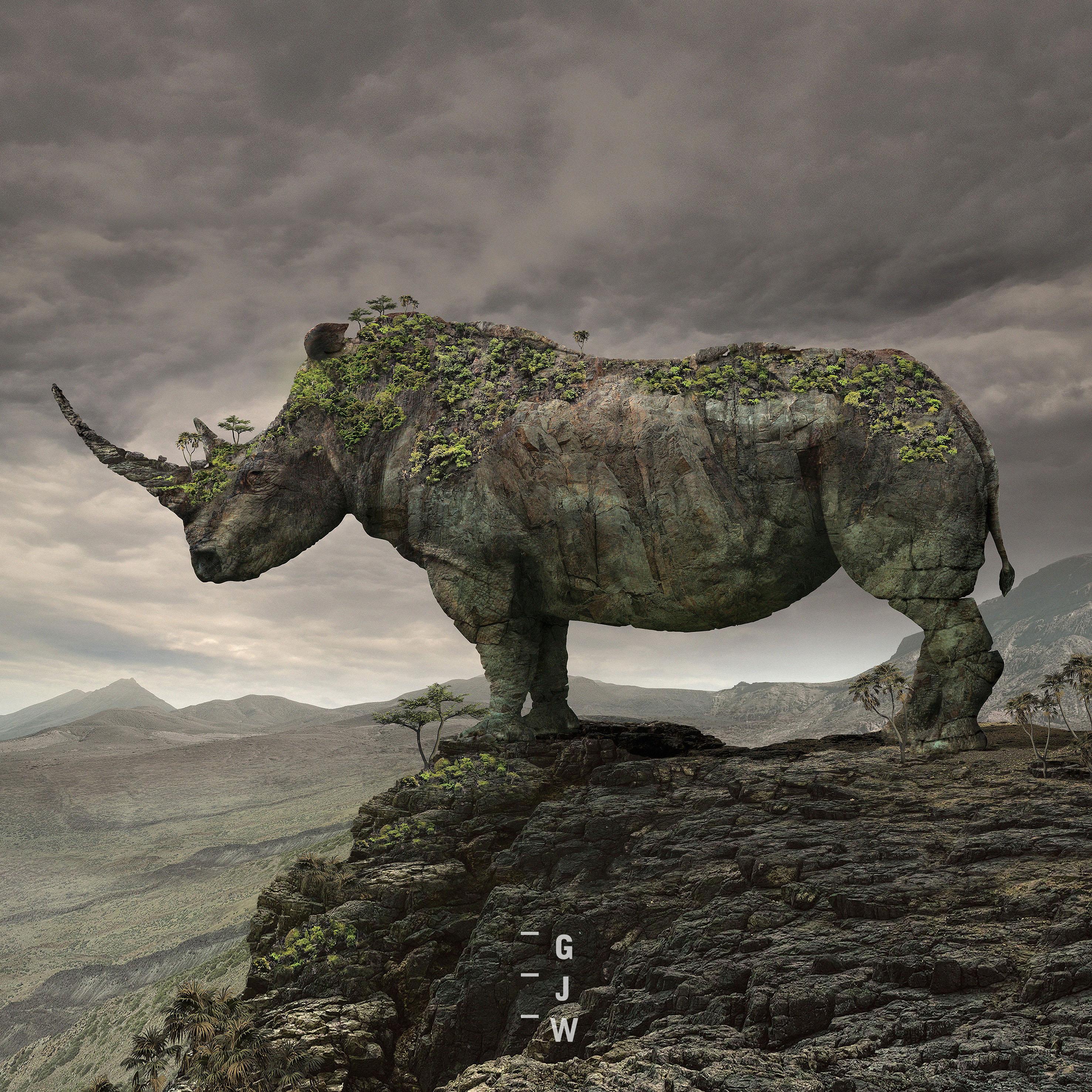 nosorożec ze skały obrośnięty lasem na tle skalistego i pochmurnego krajobrazu